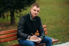 Ein Student in einer schwarzen Jacke sitzt in einem Park auf einer Bank notiert seine Gedanken in einem Notizbuch Stattlicher Jun Stockfotografie