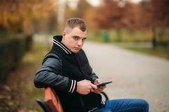 Ein Student in einer schwarzen Jacke sitzt in einem Park auf einer Bank notiert seine Gedanken in einem Notizbuch Stattlicher Jun Lizenzfreie Stockbilder