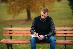 Ein Student in einer schwarzen Jacke sitzt in einem Park auf einer Bank notiert seine Gedanken in einem Notizbuch Stattlicher Jun Lizenzfreies Stockfoto