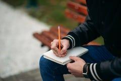 Ein Student in einer schwarzen Jacke sitzt in einem Park auf einer Bank notiert seine Gedanken in einem Notizbuch Stattlicher Jun Lizenzfreie Stockfotos