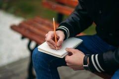 Ein Student in einer schwarzen Jacke sitzt in einem Park auf einer Bank notiert seine Gedanken in einem Notizbuch Stattlicher Jun Stockbild