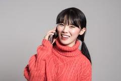 Ein Studioporträt einer Zwanziger Jahre Asiatin, die glücklich einen Telefonanruf empfängt Stockfoto