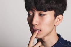 Ein Studioporträt eines asiatischen jungen Mannes, der beunruhigt und im Gedanken tief ist stockbilder