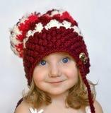 Ein Studioporträt eines lächelnden kleinen Mädchens in einer purpurroten Strickmütze Lizenzfreie Stockbilder