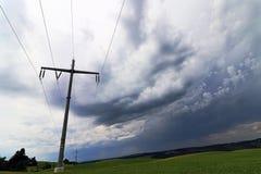 Ein Sturm im Himmel über einer obenliegenden Linie Mast Stockbilder