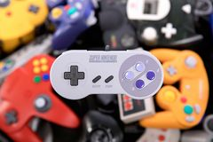Ein Super Nintendo-Kontrolleur Hovering über einem Stapel von Retro- Videospiel-Prüfern stockfotos