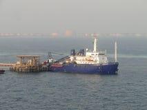 Ein Supertanker kombinierte, Lasten des Öls in der Offshorebohrinsel Stockbild