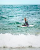 Ein surfendes Mädchen wartet auf die rechte Welle im Ozean Stockbild
