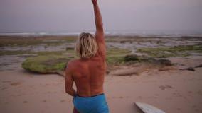 Ein Surfer, der morgens ein Training auf dem Strand tut stock video footage