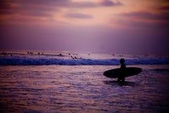 Ein Surfer am Sonnenaufgang Stockfotografie