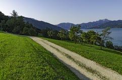 Ein szenischer Schotterweg durch den alpinen See Lizenzfreie Stockfotografie