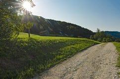 Ein szenischer Schotterweg mit Sonnenstrahlen Stockbild