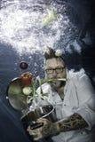 Ein tätowierter Chef, der unter Wasser mit Gemüse aufwirft Stockfoto