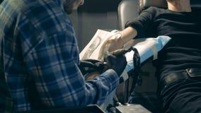 Ein Tätowierungsmeister benutzt Ausrüstung beim Tätowieren der Handprothese stock video footage