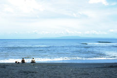 Ein Tag auf dem Ozean und dem Strand mit schwarzem Sand Lizenzfreie Stockfotos