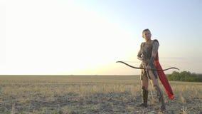 Ein tapferer Bogenschütze in der Rüstung und in einem roten Mantel steht mit einem ausgedehnten Bogen und betrachtet die Kamera,