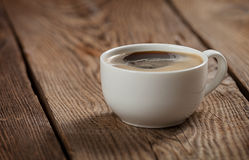 Ein Tasse Kaffee auf dem Tisch der alten Bretter lizenzfreie stockfotografie
