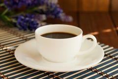 Ein Tasse Kaffee auf einem hölzernen Hintergrund Lizenzfreie Stockfotos