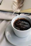 Ein Tasse Kaffee auf einem Hintergrund des Notizblockes mit einer Feder stockbild