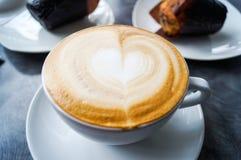 Ein Tasse Kaffee auf einer Tabelle mit einem Bild des Herzens Lizenzfreies Stockbild