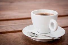 ein Tasse Kaffee auf einer Untertasse und einem Löffel steht auf einem Holztisch aromatischer heißer frischer Kaffee hölzerner We lizenzfreies stockbild