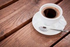 ein Tasse Kaffee auf einer Untertasse und einem Löffel steht auf einem Holztisch aromatischer heißer frischer Kaffee hölzerner We lizenzfreie stockbilder