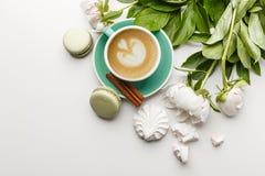 Ein Tasse Kaffee auf einer weißen Tabelle mit Pfingstrosen, Bonbons und Früchten lizenzfreie stockfotografie