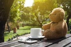 ein Tasse Kaffee auf Tabelle und Puppe im Garten am sonnigen Tag Lizenzfreie Stockbilder