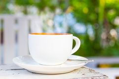 Ein Tasse Kaffee auf weißer Tabelle mit grünem Naturhintergrund, Lattekunst des Kaffees stockfotografie