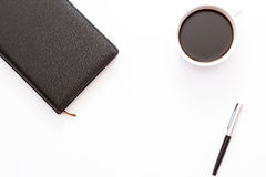 Ein Tasse Kaffee, ein schwarzes Tagebuch und ein Stift auf einem weißen Hintergrund Minimales Geschäftskonzept des Arbeitsplatzes Lizenzfreie Stockbilder