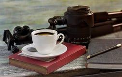 Ein Tasse Kaffee, ein Stativ und Linse auf Holztischkonzept für t Stockfoto