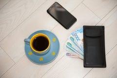 Ein Tasse Kaffee, eine Geldbörse und eine Handylüge auf einem hölzernen Stand stockfotos