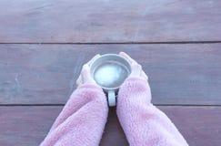 Ein Tasse Kaffee in einer Frau ` s Hand auf einem Holztisch Lizenzfreie Stockfotografie