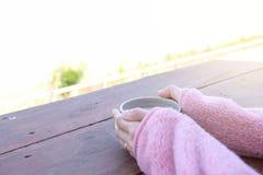 Ein Tasse Kaffee in einer Frau ` s Hand auf einem Holztisch Stockfoto
