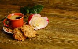 Ein Tasse Kaffee, Kekse und eine Rose auf einem hölzernen Hintergrund Stockfotografie