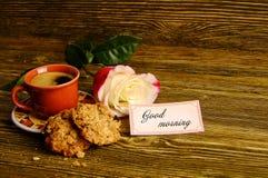 Ein Tasse Kaffee, Kekse und eine Rose auf einem hölzernen Hintergrund Stockbild