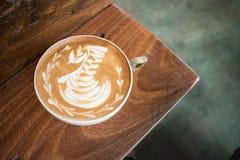 Ein Tasse Kaffee Latte-Kunstschwan in der Ecke eines Holztischs stockfotografie