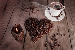 Ein Tasse Kaffee mit Herzen formte Stapel des Kaffees und der coffe Kerze Stockfoto