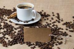 Ein Tasse Kaffee mit Kaffeebohnen und Aufkleber Lizenzfreie Stockbilder