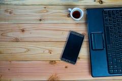 ein Tasse Kaffee mit labtop und ein Stift mit Buch auf hölzernem Schreibtisch lizenzfreie stockfotos