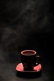 Ein Tasse Kaffee mit Rauche auf schwarzem Hintergrund getont Stockbild