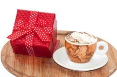 Ein Tasse Kaffee mit Sahne und rote Geschenkbox mit Bogen Lizenzfreies Stockfoto