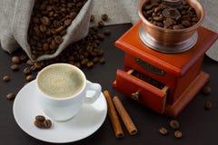 Ein Tasse Kaffee nahe Röstkaffeebohnen und einer Kaffeemühle Stockfotografie