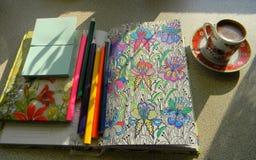 Ein Tasse Kaffee, ein Notizbuch für Kreativität, Bleistifte und ein Notizbuch auf dem Tisch Stockbilder