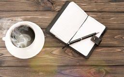 Ein Tasse Kaffee Notizbuch, Notizbuch, Stift auf dem Hintergrund Stockbilder