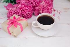Ein Tasse Kaffee, rosa Pfingstrosen Muster und eine Geschenkbox auf hölzernem Hintergrund Stockbilder