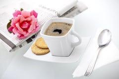 Ein Tasse Kaffee schließen durch eine Zeitung und eine Rose ein Stockfotos