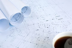 Ein Tasse Kaffee und Architekturpläne auf Funktionstabelle stockfotos