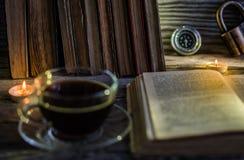 Ein Tasse Kaffee und auf dem Tisch ausgebreitet dem Buch lizenzfreies stockbild