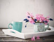 Ein Tasse Kaffee und ein Blumenstrauß von Blumen auf einem Holztisch Stockbilder
